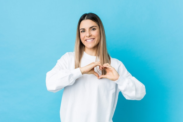 Young woman smiling and showing a heart shape with hands