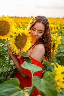 Young woman smiling at sunset in a field of sunflowers a cute girl of caucasian appearance in a red ...