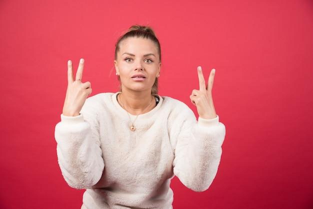 Молодая женщина улыбается в камеру и показывает пальцы, делая знак победы