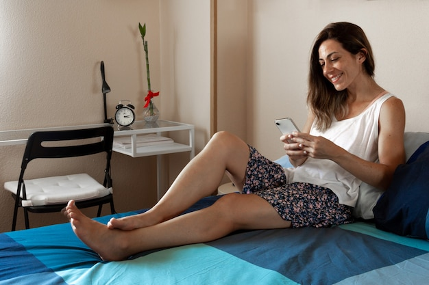 部屋のベッドに横たわっているスマートフォンを使用して笑っている若い女性セレクティブフォーカスコピースペース