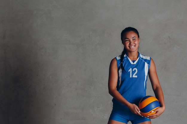Young woman smiling volleyball player with ball.