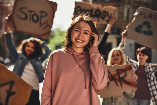 길에서 여성 활동가 그룹과 함께 생태에 대해 항의하면서 웃고 있는 젊은 여성