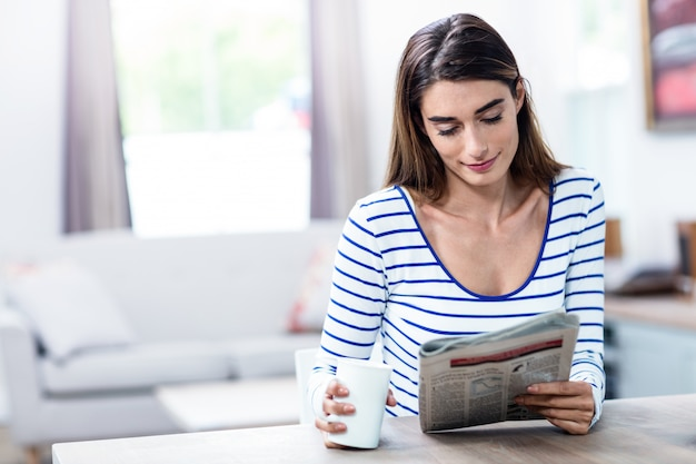 Young woman smiling while reading newspaper