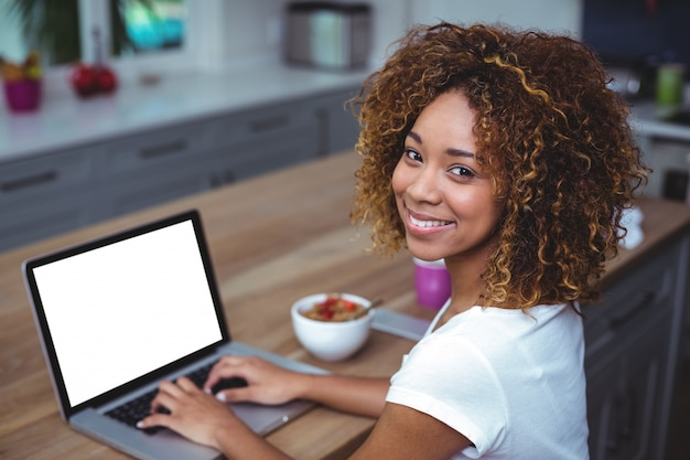 Young woman smiling while using laptop in kitchen