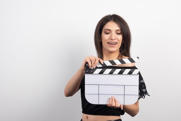 Молодая женщина улыбается с с 'хлопушкой' кино.