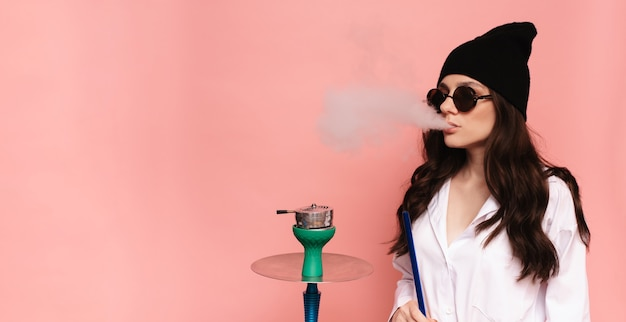 A young woman smokes a hookah