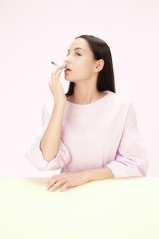 The young woman smoking cigarette while sitting at table at studio. trendy colors. the portrait of caucasian girl in minimalism style with copy space