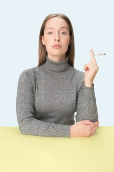 The young woman smoking cigarette while sitting at table at