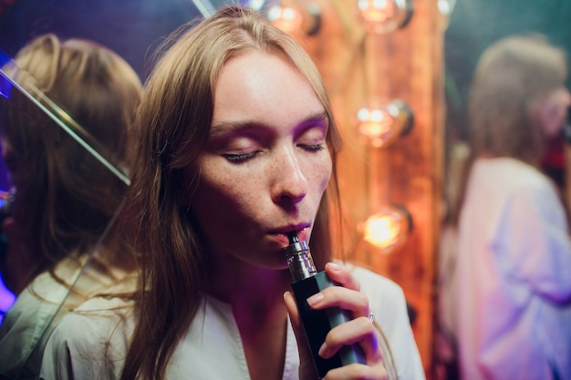 Young woman smoking electronic cigarette against background of mirrors