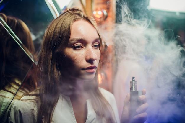 Молодая женщина курит электронную сигарету на фоне зеркал