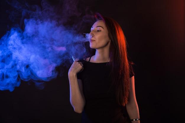 Молодая женщина курит электронную сигарету, сигаретный дым в свете
