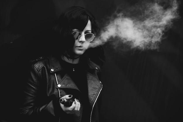 Молодая женщина курит электронную сигарету