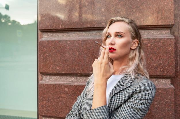 Молодая женщина курит на открытом воздухе