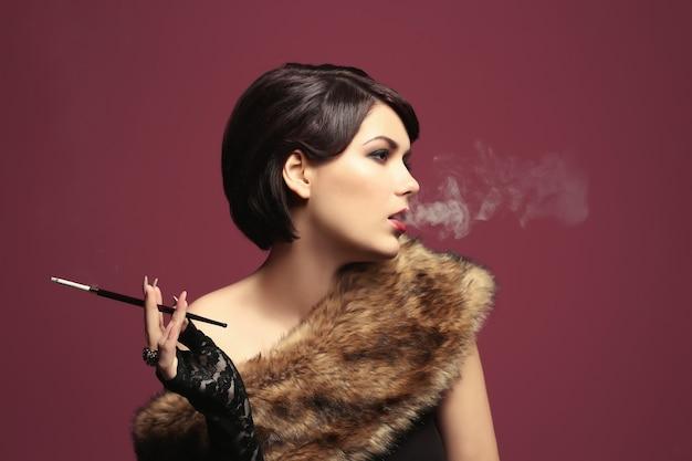 色の上のタバコホルダーと喫煙若い女性