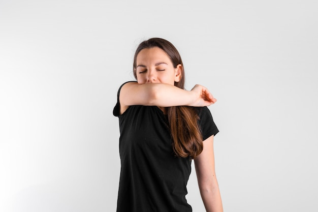 Young woman sneezing to elbow. pneumonia or virus sickness. covid-19 pandemic