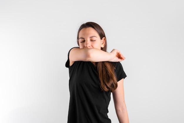 Молодая женщина чихает до локтя. пневмония или вирусная болезнь. covid-19 пандемия
