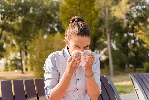 Young woman sneezing while having an allergy