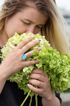 アジサイの花束を嗅ぐ若い女性