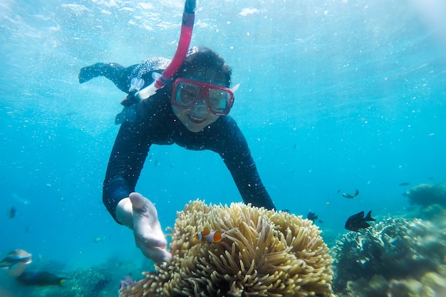 Young woman snorkeling on a beautiful reef with fish at karimun jawa beach