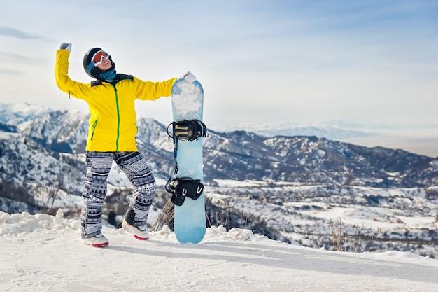 눈 덮인 산의 배경에 노란색 재킷과 검은색 헬멧을 쓴 젊은 여성 스노보더.