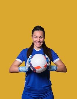 Молодой вратарь футбола женщины с мячом в руках на желтой изолированной стене