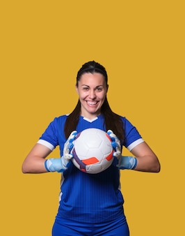 Young woman soccer goalkeeper with a ball in her hands on a yellow isolated wall