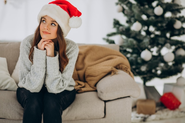 Young woman on sofa by the christmas tree