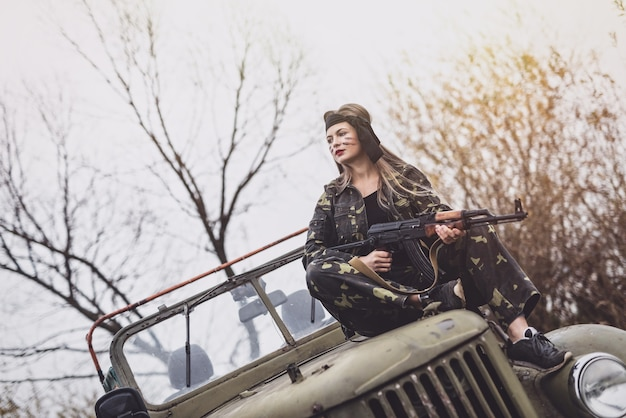 Young woman soldier with rifle posing on military car