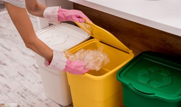 Молодая женщина сортирует мусор на кухне. концепция утилизации. ноль отходов