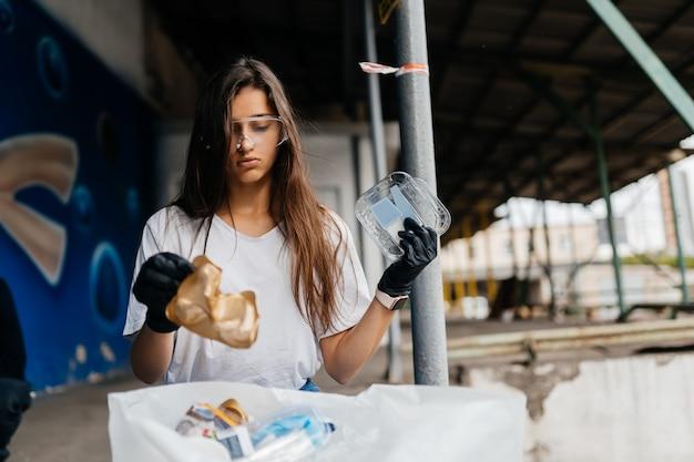 Молодая женщина, сортирующая мусор. концепция утилизации. без отходов
