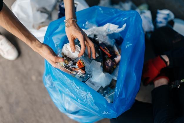 쓰레기를 정렬하는 젊은 여자. 재활용의 개념. 제로 폐기물
