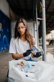 Young woman sorting garbage