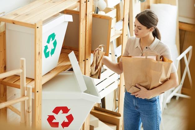 倉庫に立っている間、紙袋をプラスチック容器に分類する若い女性