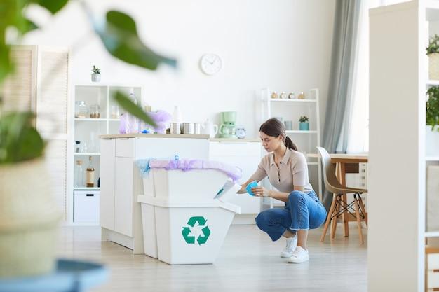 自宅の家庭用キッチンのゴミ箱に紙くずを分別する若い女性