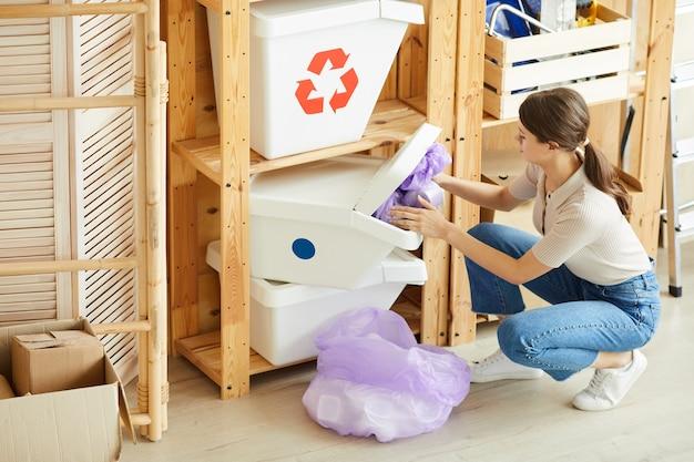 若い女性がゴミをパッケージに分類し、ゴミ箱に捨てる