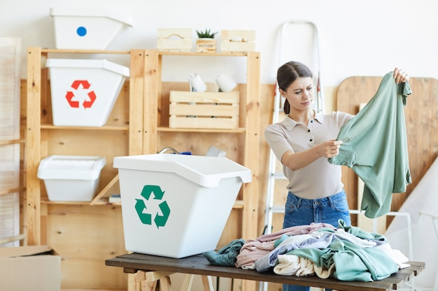 Молодая женщина сортирует старую одежду и перерабатывает ее в экологических контейнерах
