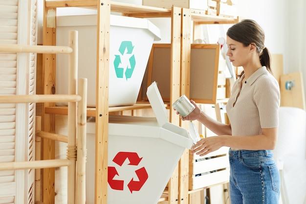 廃棄物を倉庫のプラスチック容器に分別する若い女性