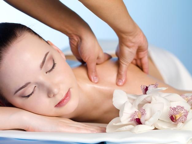 Giovane donna nel salone della stazione termale che ha massaggio della spalla - orizzontale