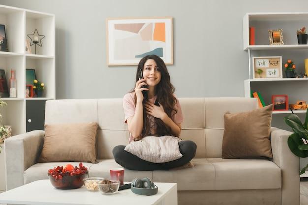 若い女性は、リビングルームのコーヒーテーブルの後ろのソファに座って電話で話します