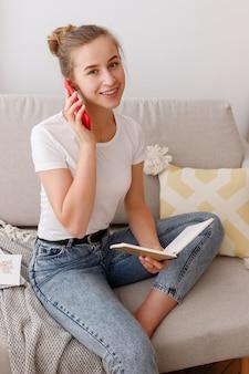 若い女性が居間で電話で話します