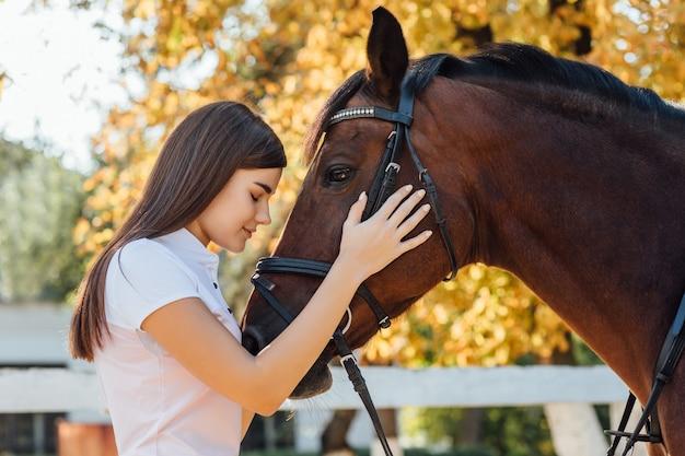 Giovane donna in uniforme speciale e cavallo. concetto di sport equestre.