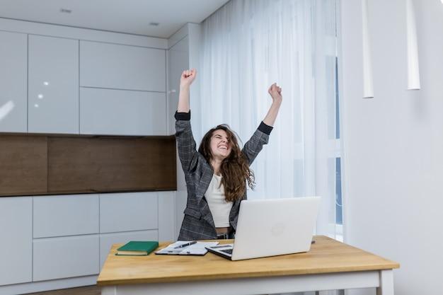 若い、女性、スペシャリストは彼の机に座って、上げられた握りこぶしで彼の完成した仕事を喜ぶ