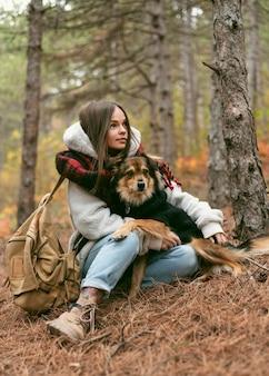 Молодая женщина проводит время вместе со своей собакой в лесу
