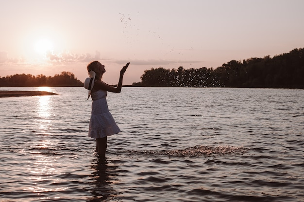 A young woman splashes water. photo of a slender, beautiful, happy blonde in a summer dress and a straw hat standing in the river against the sunset and raising her hands.
