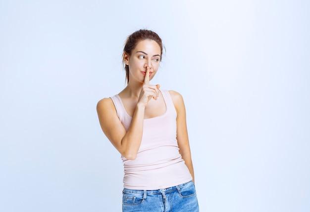 Giovane donna in camicia sportiva che chiede silenzio