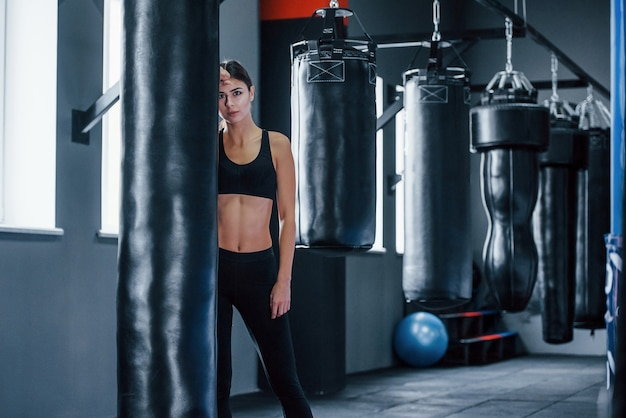 Young woman in sportive wear is in the gym having exercise day. conception of boxing.