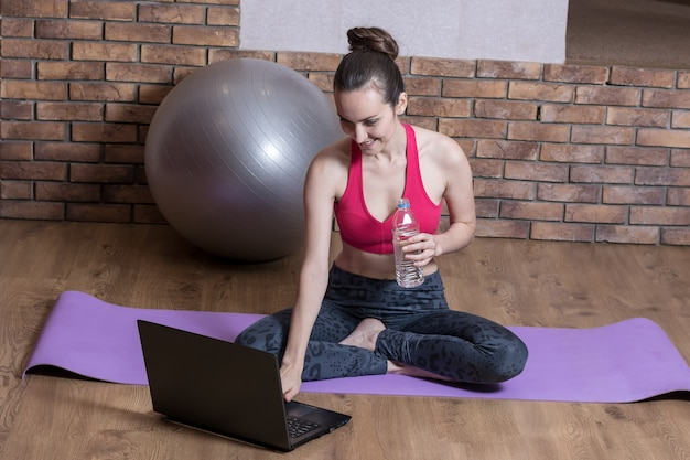 A young woman sports blogger is resting after a workout online, drinking water from a plastic bottle on the yoga mat. home fitness