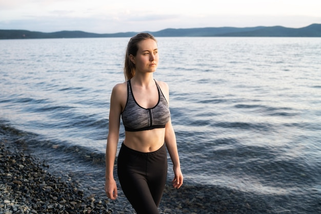 A young woman in a sports bra and leggings walks along the rocky shore of lake turgoyak during sunset