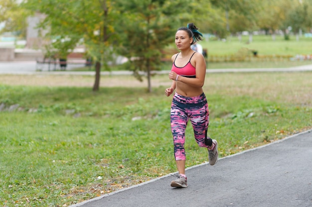 A young woman in sports clothes is running in a city park