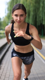Young woman in sports clothing running while exercising outdoors.